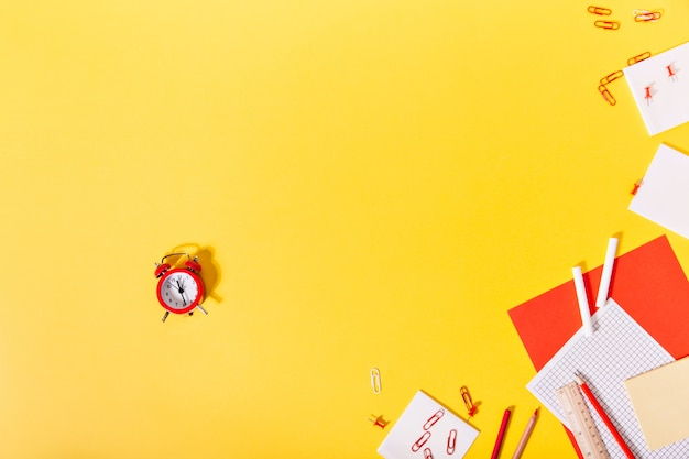 Im zentrum der ausstellung des schulbriefpapiers befindet sich ein roter kleiner wecker