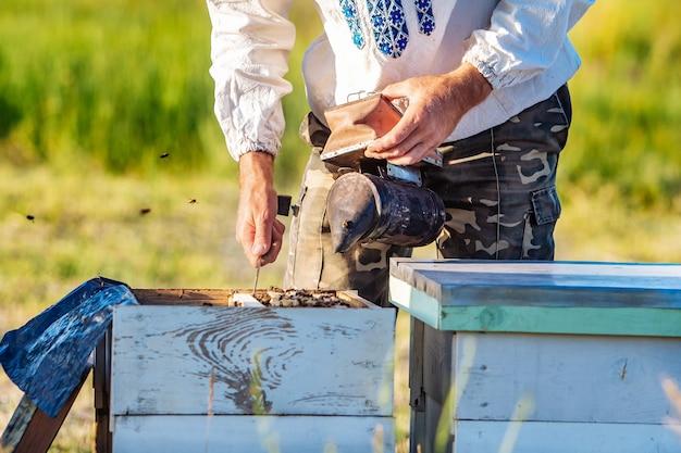 Imker arbeitet mit bienen und bienenstöcken auf der imkerei. imker auf imkerei.