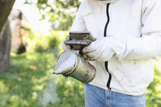 Imker, der raucher hält, um bienen zu rauchen, nahaufnahme, hobby-imkerei-konzept