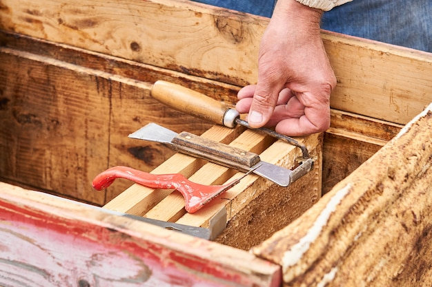 Imkerwerkzeuge und seine hand auf dem hintergrund von wabenrahmen in einem offenen bienenstock