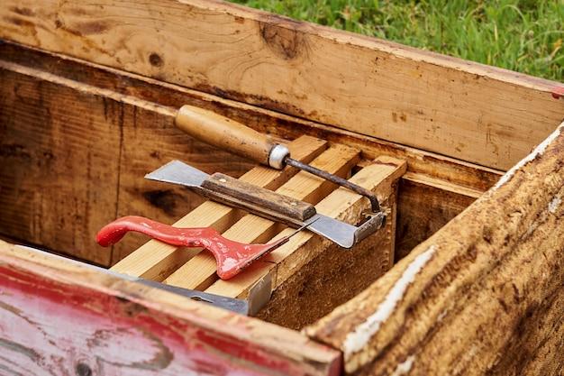 Imkerwerkzeuge werden in einem geöffneten bienenstock auf wabenrahmen ausgelegt