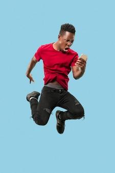 Immer auf dem handy. voller länge des hübschen afrikanischen jungen mannes, der telefon beim springen gegen blauen studiohintergrund nimmt. mobil, bewegung, bewegung, geschäftskonzepte