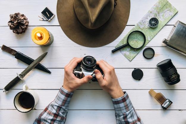 Immer bereit für eine reise draufsicht mit wandererhänden, die vintage filmkamera halten