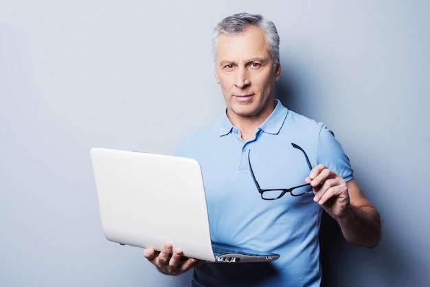 Immer bereit, ihnen zu helfen. fröhlicher älterer mann in lässiger haltung, der seine brille und seinen laptop hält, während er vor grauem hintergrund steht