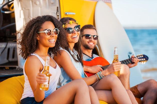 Immer glücklich zusammen. drei fröhliche junge leute, die bier trinken und gitarre spielen, während sie am strand in der nähe von retro-van sitzen?