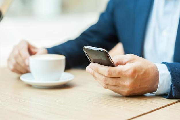 Immer in kontakt. abgeschnittenes bild eines mannes in abendkleidung, der kaffee trinkt und eine nachricht auf dem handy eingibt, während er im restaurant sitzt