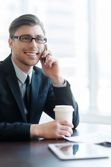 Immer in kontakt. fröhlicher junger mann in abendkleidung, der am telefon spricht und kaffee trinkt, während er im büro sitzt
