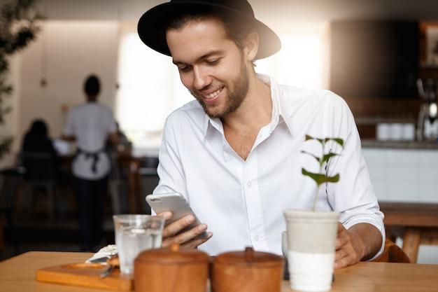 Immer in kontakt. gut aussehender, stilvoller junger hipster, der seiner freundin auf seinem generischen mobiltelefon eine sms schreibt, einen termin mit ihr vereinbart und eine hochgeschwindigkeits-internetverbindung im café nutzt