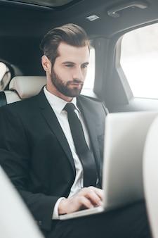 Immer in kontakt. hübscher junger geschäftsmann, der an seinem laptop arbeitet, während er im auto sitzt