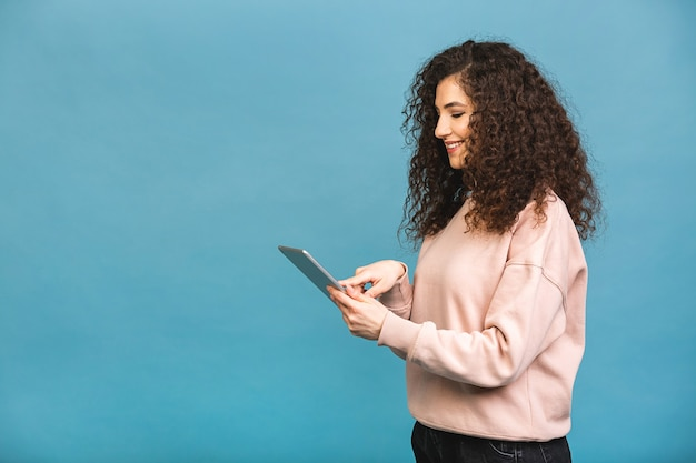 Immer in kontakt! schönes lockiges junges mädchen lächelnd unter verwendung der tablette lokalisiert über blauem hintergrund. kopieren sie platz für text.
