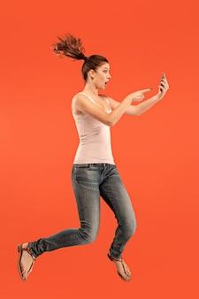 Immer mobil. volle länge der hübschen jungen frau, die telefon nimmt, während gegen roten studiohintergrund springend. mobil, bewegung, bewegung, geschäftskonzepte