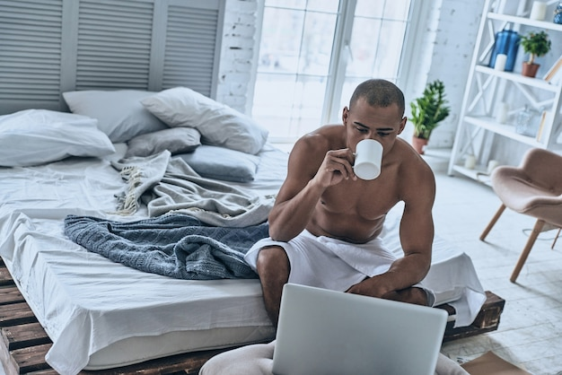 Immer online. hübscher junger afrikanischer mann bedeckt mit duschtuch, der kaffee trinkt