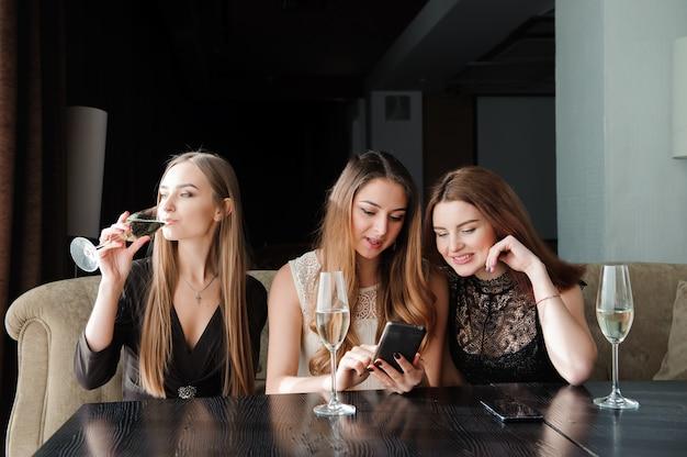 Immer verbunden, internetabhängigkeit, junge mädchen im café, die auf ihre smartphones schauen, soziales netzwerkkonzept