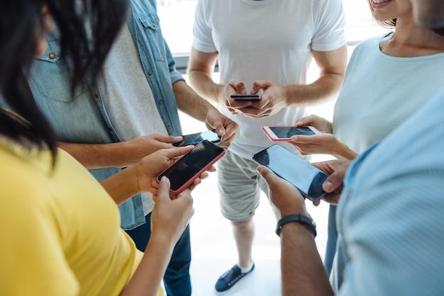 Immer verbunden. nahaufnahme von modernen smartphones, die von netten intelligenten jungen leuten benutzt werden