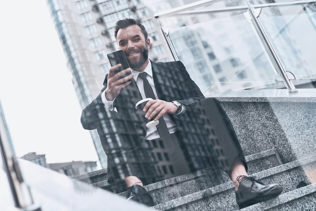 Immer verfügbar. gut aussehender junger mann im vollen anzug, der sein smartphone benutzt und lächelt