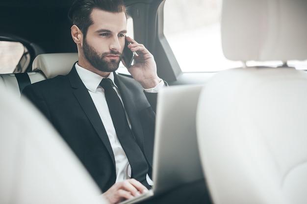 Immer verfügbar. hübscher junger geschäftsmann, der an seinem laptop arbeitet und telefoniert, während er im auto sitzt
