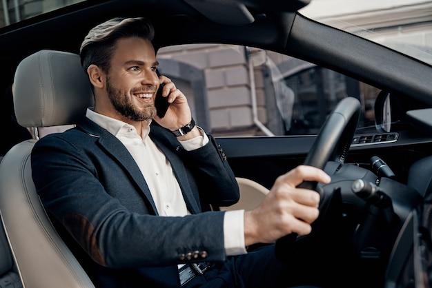 Immer verfügbar. hübscher junger mann in abendgarderobe, der auf seinem smartphone spricht und lächelt, während er ein luxusauto fährt