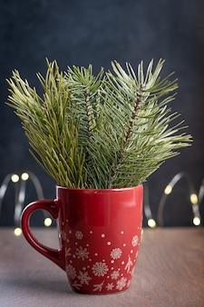 Immergrüne tannen- oder kiefernzweige mit nadeln im roten weihnachtsbecher auf dunkelbraunem holztisch