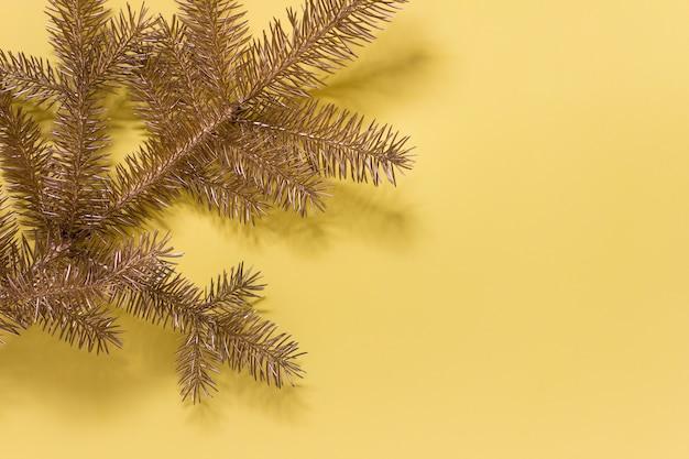 Immergrüner zweig der goldenen tanne auf gelber oberfläche. foto mit kopie leerzeichen.