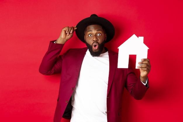 Immobilie. fröhlicher schwarzer mann, der papierhaus zeigt und lächelt, makler empfiehlt, der über rotem hintergrund steht