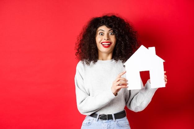 Immobilien. aufgeregte lächelnde frau, die papierhausausschnitt zeigt und erstaunt schaut, auf rotem hintergrund stehend.