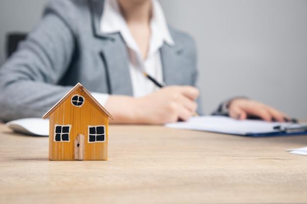 Immobilien, frau, die im dokument mit hausmodell arbeitet