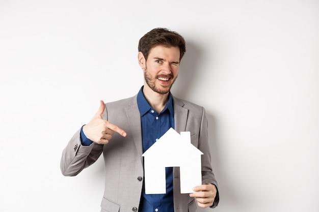 Immobilien. hübscher geschäftsmann, der zwinkert und auf papierhausausschnitt, werbefirma, steht auf weißem hintergrund zeigt.