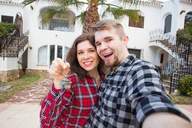 Immobilien-, immobilien- und mietkonzept - glückliches lustiges junges paar, das einen schlüssel ihres neuen hauses zeigt