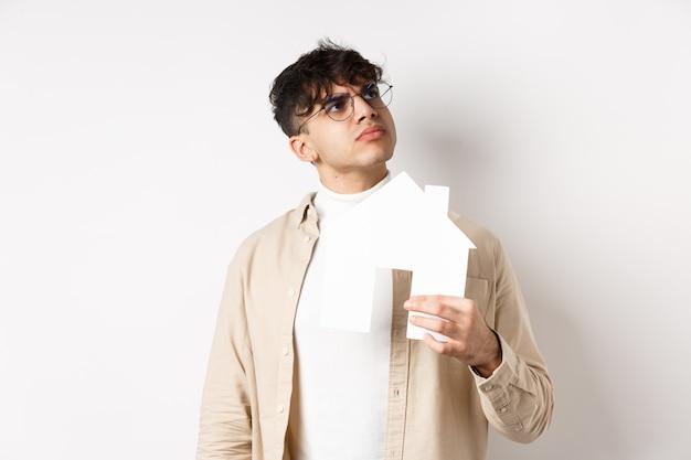 Immobilien- und hypothekenkonzept. nachdenklicher junger mann, der an neue wohnung denkt, papierhausausschnitt hält und logo der oberen rechten ecke betrachtet, auf weißer wand stehend.