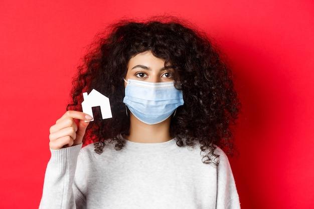 Immobilien- und pandemiekonzept. junge frau in der medizinischen maske, die kleinen papierhausausschnitt zeigt, der auf rotem hintergrund steht.