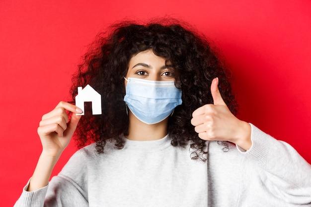 Immobilien- und pandemiekonzept. nahaufnahme der frau, die agentur empfiehlt, medizinische maske trägt, daumen hoch und papierhausausschnitt zeigt, roter hintergrund.