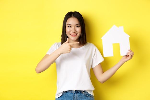 Immobilien- und versicherungskonzept. fröhliche asiatische frau, die lächelt, auf papierhausausschnitt zeigt, agenturlogo empfehlen, auf gelbem hintergrund stehend.