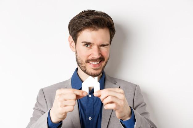 Immobilien- und versicherungskonzept. hübscher mann im anzug, der zwinkert und lächelt und kleinen papierhausausschnitt zeigt, der auf weißem hintergrund steht.