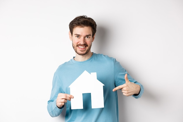 Immobilien- und versicherungskonzept. lächelnder junger mann, der auf papierhausausschnitt zeigt und glücklich schaut, wohnung kaufen, über weißem hintergrund stehend.