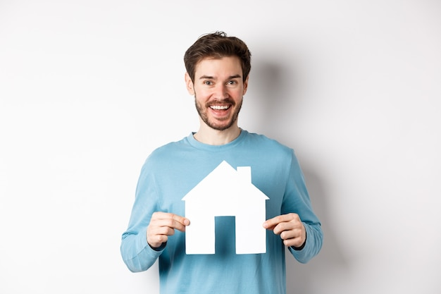 Immobilien- und versicherungskonzept. schöner moderner mann, der immobilien kauft, lächelt und zeigt papierhausausschnitt, stehend über weißem hintergrund