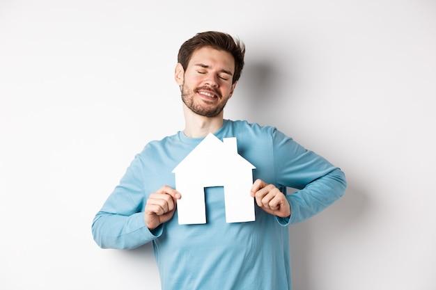 Immobilien- und versicherungskonzept. verträumter junger mann, der mit geschlossenen augen lächelt, papierhausausschnitt zeigt, haus kaufen möchte, über weißem hintergrund stehend.