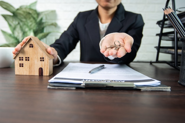 Immobilien- und vertragsunterzeichnung, verkäufer und käufer von eigenheimen verhandeln erfolgreich und erzielen eine einigung und geben dem eigentümer den eigenheimschlüssel
