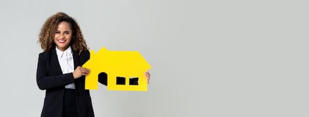 Immobilienagentur der afroamerikanerfrau, die papierhaus hält