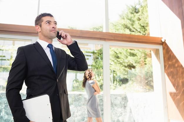Immobilienagentur, die am handy und am kunden betrachten die wohnung spricht