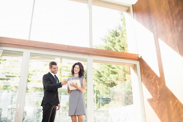Immobilienagentur, die auf die junge frau zeigt neues haus einwirkt