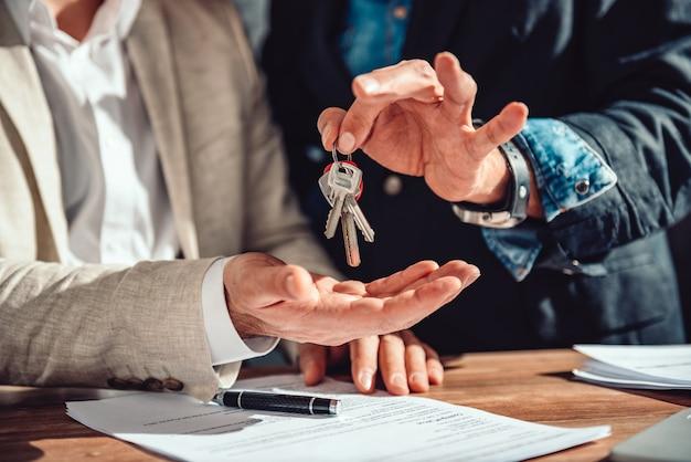 Immobilienagentur, die einem kunden wohnungsschlüssel übergibt