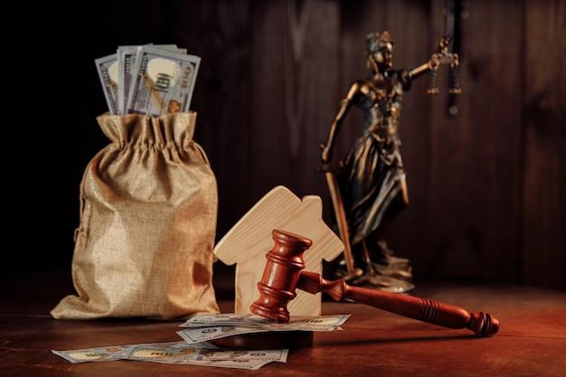 Immobilienauktionskonzept, geldsack mit bargeld, haus- und richterhammer mit dame der gerechtigkeit.