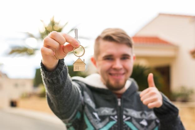 Immobilienbesitz neues zuhause und menschenkonzept junger mann, der in ein neues zuhause einzieht