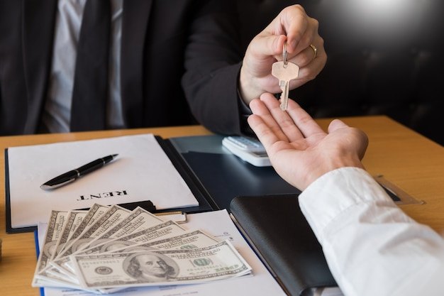 Immobilienentwickler agent und unterzeichnen auf dem dokument, das schlüssel des neuen hauses gibt