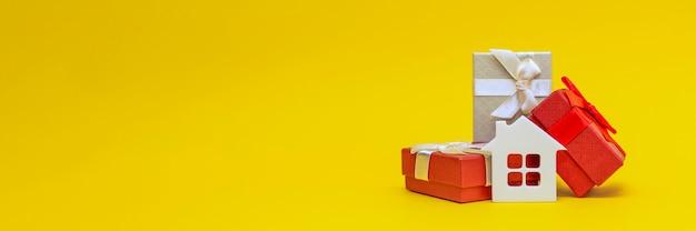 Immobiliengeschenk, hausgeschenk. weißes spielzeughaus in einer geschenkbox auf gelbem grund. postkarte zum drucken, banner mit platz für text.