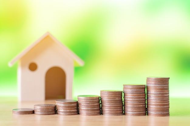 Immobilieninvestition und haushypothek finanzkonzept geldmünzenstapel mit holzhaus