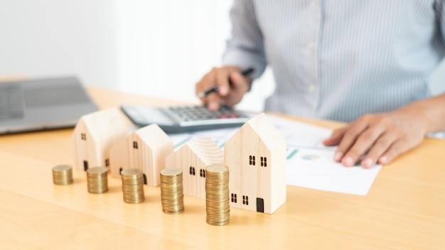 Immobilieninvestition und haushypothek finanzkonzept, hand eines geschäftsmannes, der münzen für immobilieninvestitionen stapelt, für den kauf für wohnraum oder spekulation spart.