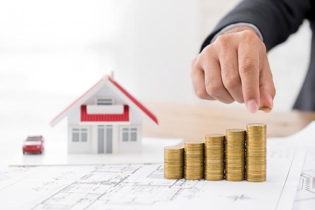 Immobilieninvestor, der gewinnwachstum des wohnbebauungsplans unter verwendung der münzen projektiert