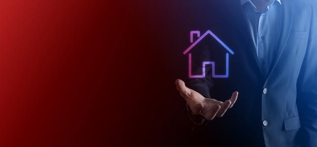 Immobilienkonzept, geschäftsmann, der ein haussymbol hält. haus zur hand. sachversicherung und sicherheit