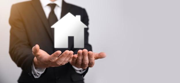 Immobilienkonzept, geschäftsmann, der ein haussymbol hält. haus zur hand. sachversicherung und sicherheitskonzept. schützende geste des menschen und symbol des hauses.